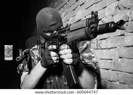 Shutterstock Black & white photo of terrorists attack with assault rifle.Military men in black balaclava masks targeting with machine guns.Airsoft team training in ruins.Guerrilla soldiers fight with firearms