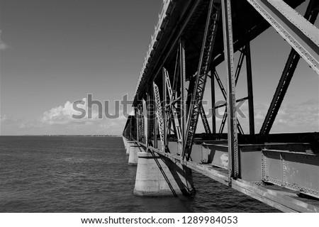 Black & white photograph of the Bahia Honda Rail Bridge, one of the famous historic landmarks in the Florida Keys #1289984053