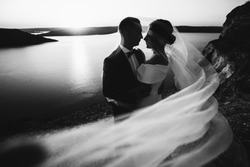 Black-white portrait of a couple kissing under a veil on a sunset background, wearing a black tuxedo and a white dress, looking into the eyes