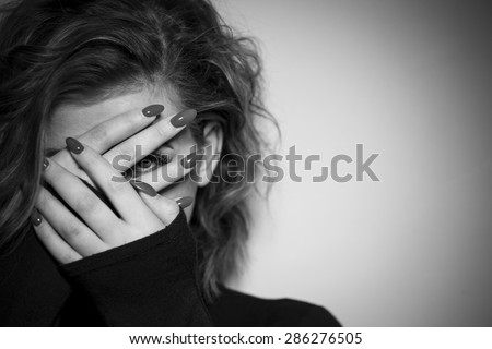 Black & White portrait of a young women hiding her face with her hands