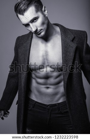 Black&white portrait of handsome shirtless young man in a coat. Perfect hair & skin. Close up. Studio shot