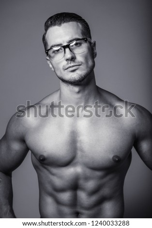 Black&white portrait of handsome shirtless young man in glasses. Perfect hair & skin. Close up. Studio shot