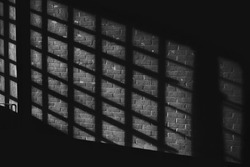 Black white quadratic shadow on a stonework wall illuminated by late sunlight - concept dramatic contrast film noir mystic interior texture background surface structure window close up detail evening