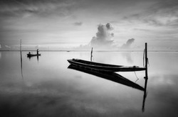 Black & white scenery of traditional fishing boat at Tumpat, Malaysia with fisherman silhouette standing on the boat. Soft focus due to long exposure.