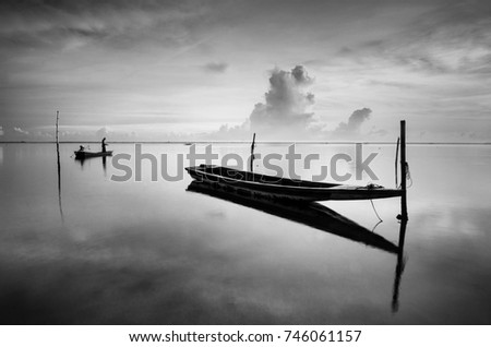 Black & white scenery of traditional fishing boat at Tumpat, Malaysia with fisherman silhouette standing on the boat. Soft focus due to long exposure.   #746061157