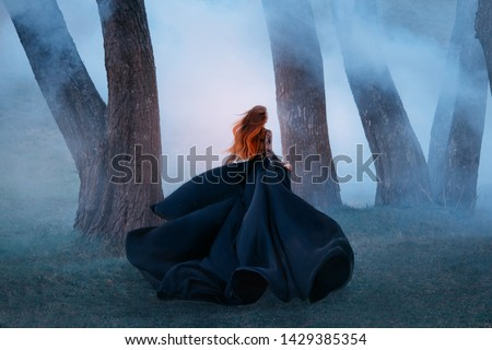 black widow long dark silk fly fabric dress, scary horror woman red hair runs mystery forest turned away black lady night walk gothic blue fog nature tree. art photo shoot mysterious woman silhouette