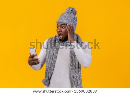 Black winter guy got shocking news, looking at smartphone screen, good deals for mobile internet, yellow background