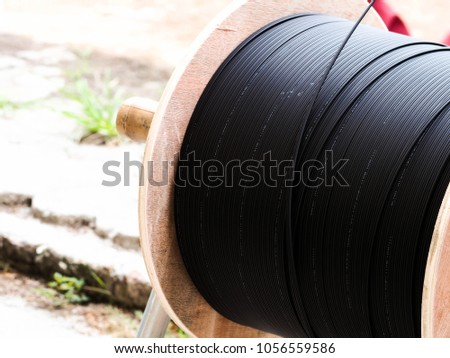 Black wire electric cable with wooden coil of electric cable. Electric cable for industy. #1056559586