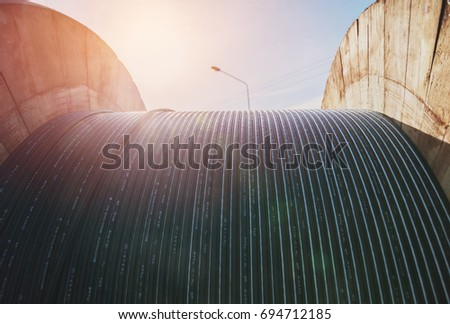 black wire  electric cable with wooden coil of electric cable under the sky. #694712185