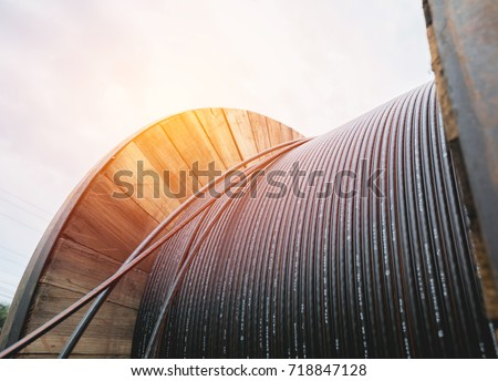 black wire  electric cable with wooden coil of electric cable under the sky. #718847128