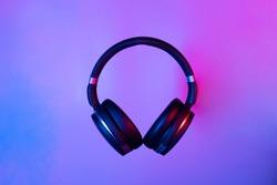 Black wireless bluetooth headphones on neon light background. Music concept.