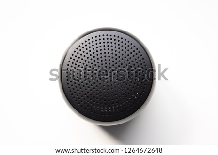 Black Wireless Bluetooth Speaker Isolated on Plain White Background, Viewed From Above; Top View Showing Perforated Metal Grille Holes.