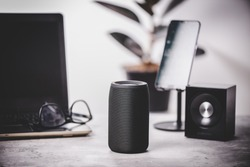 Black wireless portable bluetooth speaker for music listening. Voice assistant speaker at home.