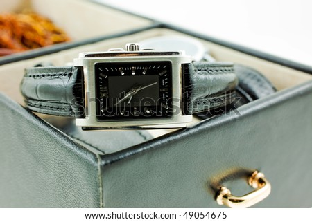 black with silver female watch in a jewelery case. white background