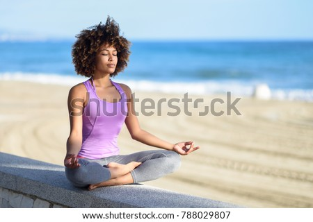 Black woman, afro hairstyle, doing yoga asana in the beach with eyes closed. Young Female wearing sport clothes in lotus pose with defocused background.