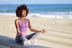 Black woman, afro hairstyle, doing yoga in the beach with eyes closed. Young Female wearing sport clothes in lotus figure with defocused background.