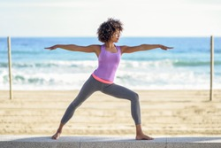 Black woman, afro hairstyle, doing yoga in warrior pose in the beach. Young Female wearing sport clothes with sea at the background