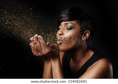 black woman blowing golden dust. Make a wish concept