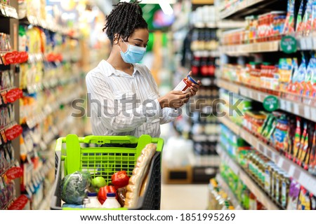Black Woman Checking Expiration Date On Food Product Doing Grocery Shopping In Supermarket Groceries Store, Standing In Aisle With Shop Trolley. Lady Buyer Choosing Healthy Food Concept