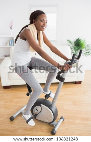 Black woman doing exercise bike while smiling in a living room