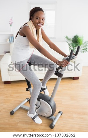 Black woman doing exercise bike with headphones in a living room
