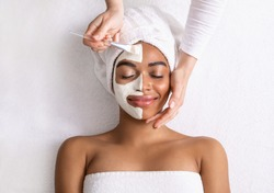 Black woman having white clay mask on half of her face, top view