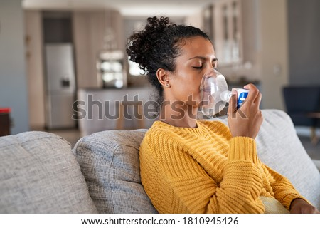 Black woman holding a mask nebulizer inhaling fumes medication into lungs. African sick lady inhaling through inhaler mask at home. Self treatment of the respiratory tract using inhalation nebulizer.
