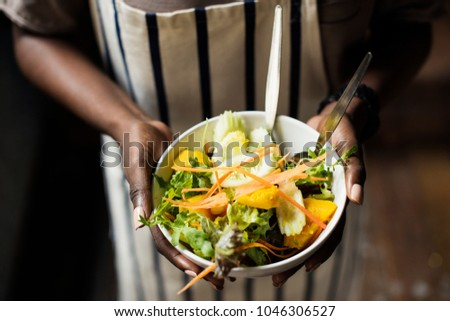 Black woman holding the salad bowl