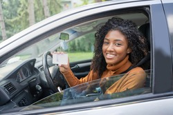 Black woman holding up driving license to her first new car. Customer satisfaction