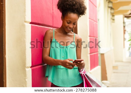 Black woman in Casco Antiguo - Panama City with shopping bags. The girl leans on a wall and types message with her phone on social network.