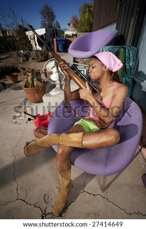 Black woman kissing rifle in front of house with messy yard