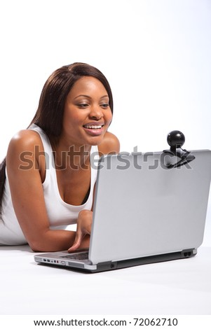 Black woman lying on floor using laptop and web cam