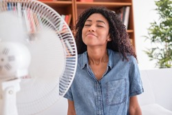 Black woman refreshing in front of a fan during summer heat
