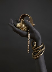 Black woman's hand with gold jewelry. Oriental Bracelets on a black painted hand. Gold Jewelry and luxury accessories on black background closeup. High Fashion art concept