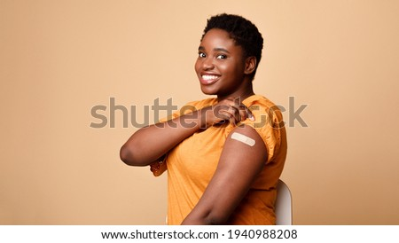 Black Woman Showing Vaccinated Arm After Vaccine Injection, Beige Background