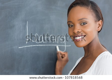 Black woman smiling while looking at camera in a classroom