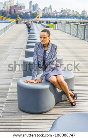 stock-photo-black-woman-thinking-outside-dressing-in-a-gray-patterned-faux-fur-jacket-a-woolen-fitted-dress-188088947.jpg