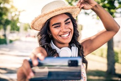 Black woman tourist taking selfie with mobile smart phone outdoor - Happy travel blogger sharing live video on social media - Vacations and travel bloggers concept