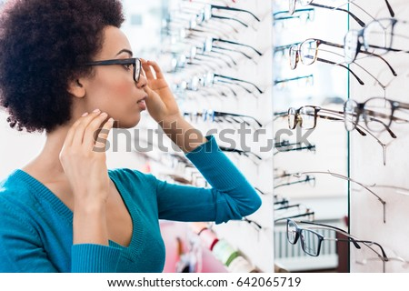 Black woman trying on glasses she wants to buy in optician store #642065719