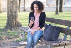 Black woman using app on mobile phone in the city park