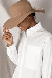 Black woman wearing a wide brim beach hat