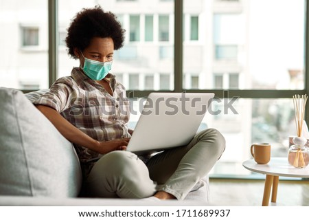 Black woman wearing face mask while working on a computer at home during virus epidemic.