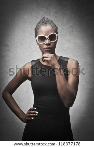 Black woman, with a pair of white sunglasses, posing in black