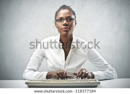 Black woman, with a white shirt, using a computer keyboard