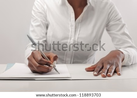 Black woman, with a white shirt, writing