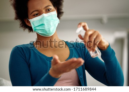 Black woman with face mask using hand sanitizer at home during virus pandemic.