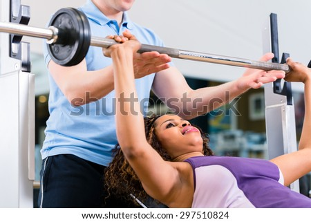 Black woman with Trainer lifting weights on barbell in gym for fitness