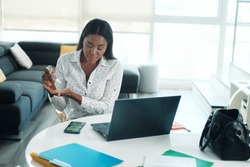 Black Woman Working From Home Using Hand Sanitizer