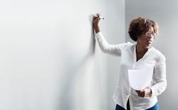 Black woman writing on a whiteboard