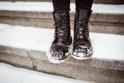 Black women's shoes on the stone steps covered by snow in the winter.